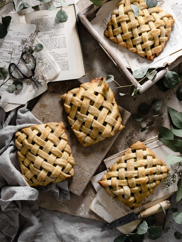 Four lattice apple hand pies on board.