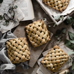 Four lattice apple hand pies on board.