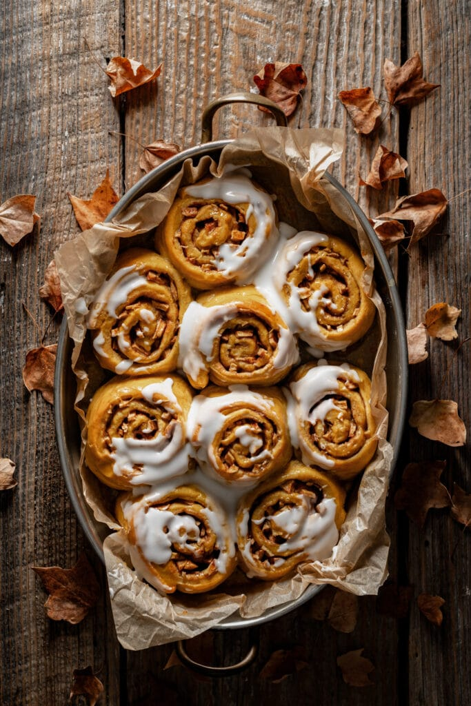 Tray filled with pumpkin sweet rolls topped with frosting.
