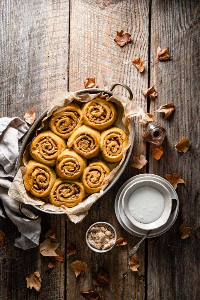 Tray of baked pumpkin cinnamon rolls on wooden table.