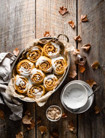 Tray of pumpkin cinnamon rolls covered in frosting.