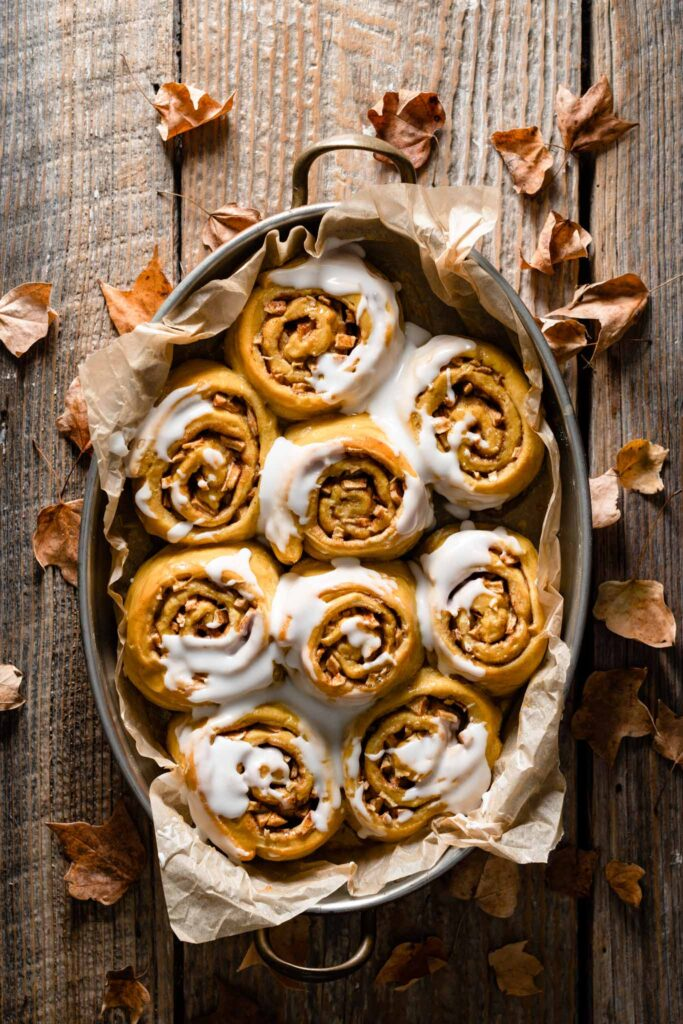 Tray of baked pumpkin cinnamon rolls covered in frosting on table.