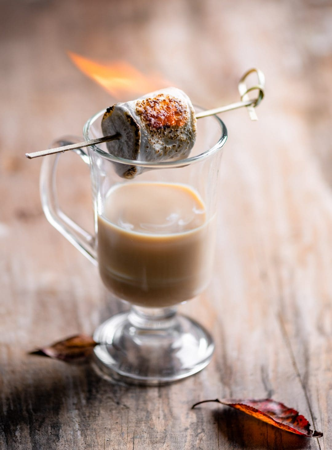 Rum cocktail with a flaming marshmallow on top.