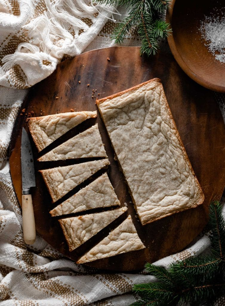 White Chocolate Blondies sliced into triangles on a wood board.