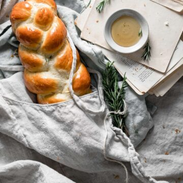 Braided loaf of bread wrapped in linen.