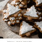 Recipe card for royal icing and a stack of christmas tree cookies.