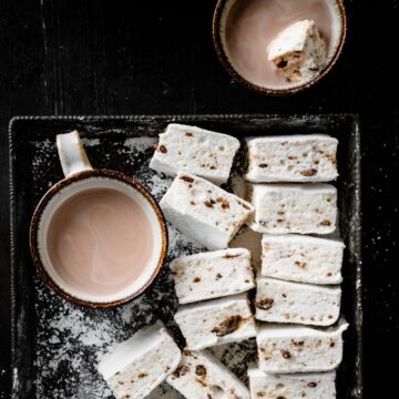 Flavored marshmallows sliced in a tray with hot chocolate.