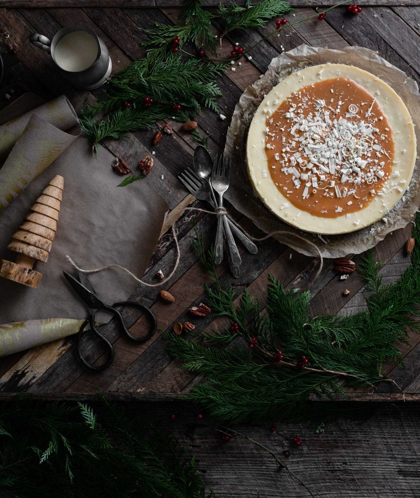 White chocolate cheesecake topped with caramel on Christmas table.