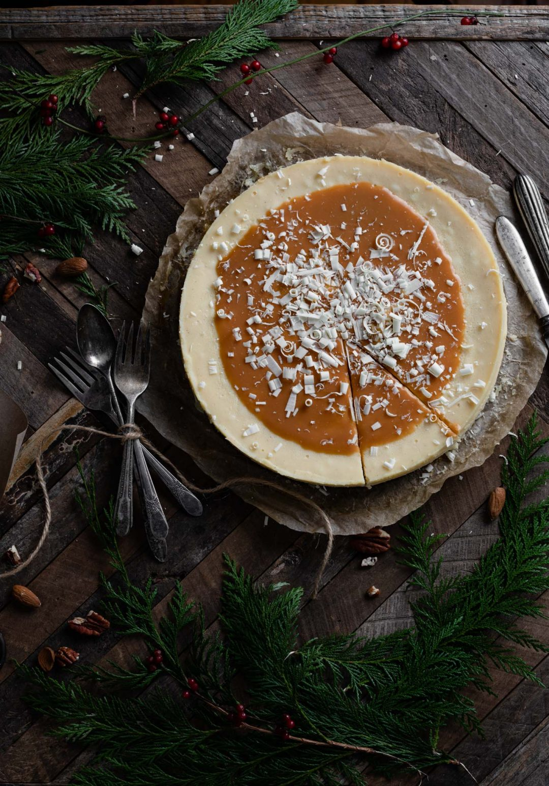 Caramel topped cheesecake on wood table with a slice cut.