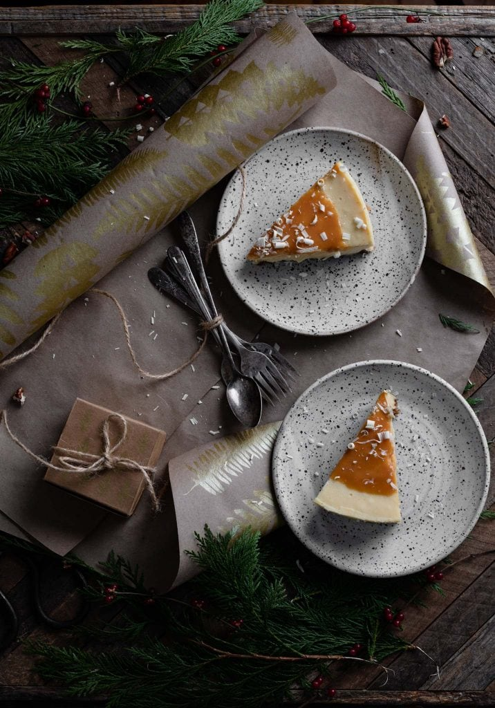 Two pieces of cheesecake eon plates next to Christmas wrapping paper on table.