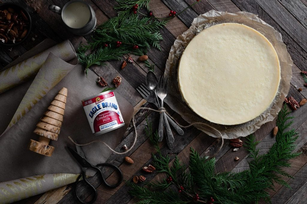 White chocolate cheesecake on table with Christmas wrapping.