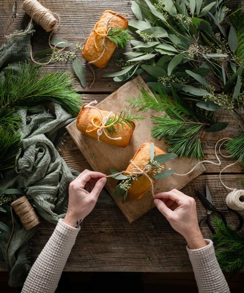 Orange cakes being wrapped with string and greenery.