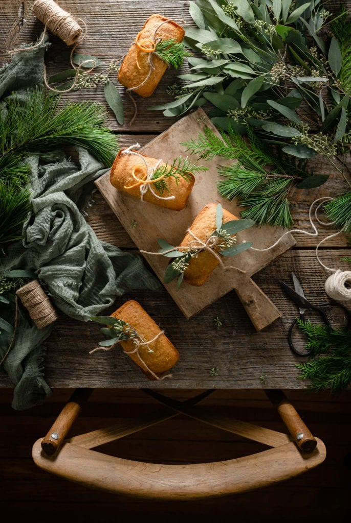 Orange ginger cakes on table wrapped in twine and greenery.