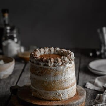 Frosted Tiramisu layer cake with piped whipped cream on cake stand.