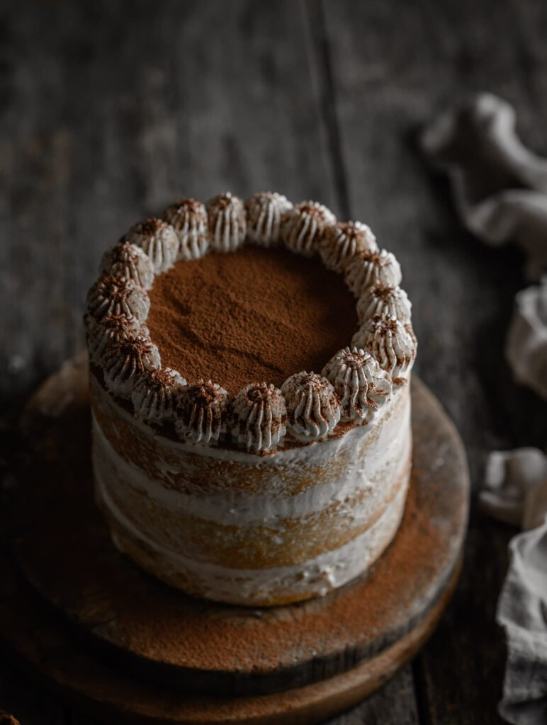 Tiramisu cake on a serving board topped with cocoa.