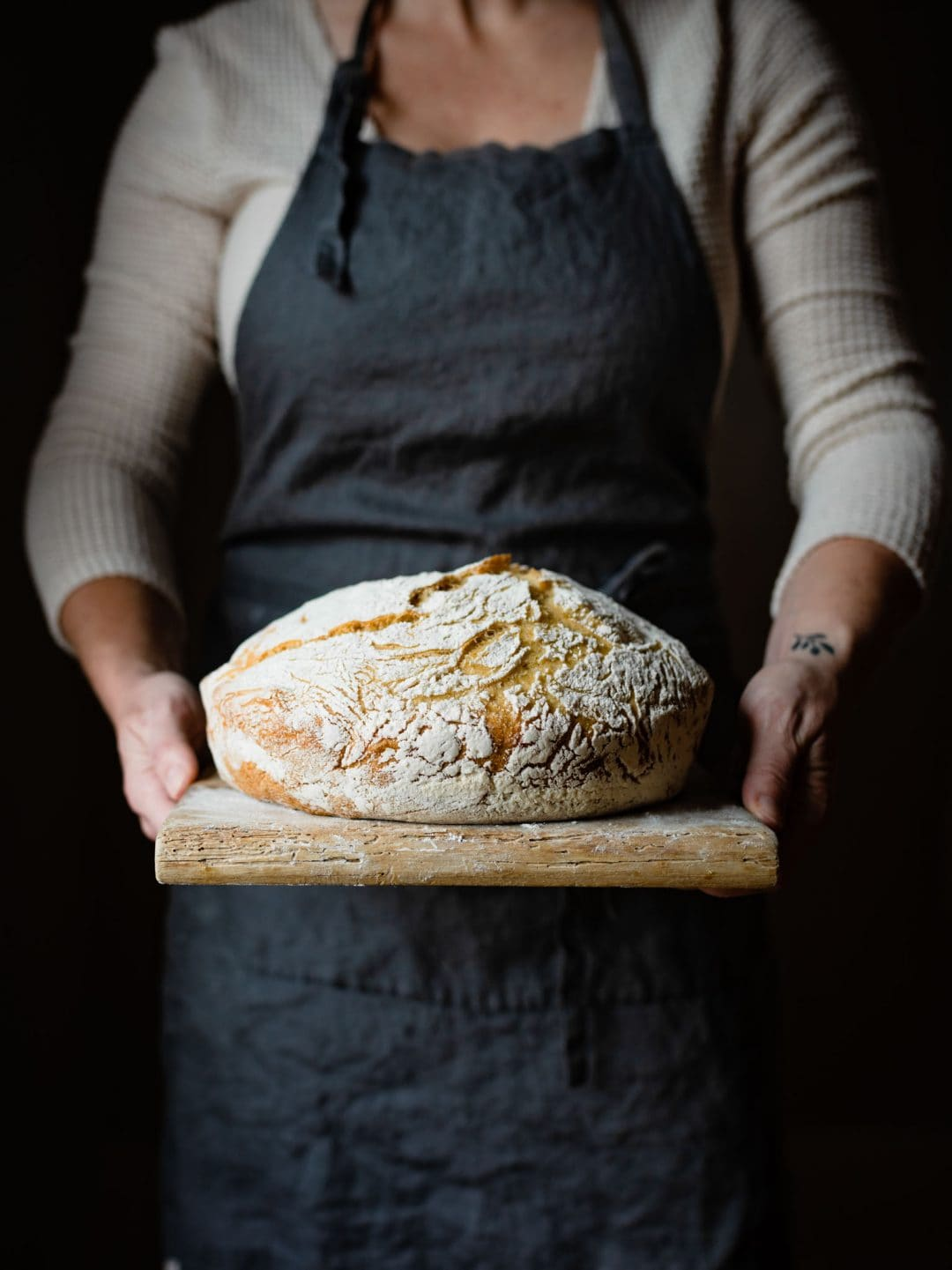Chef holding a country bread loaf on a cutting board.