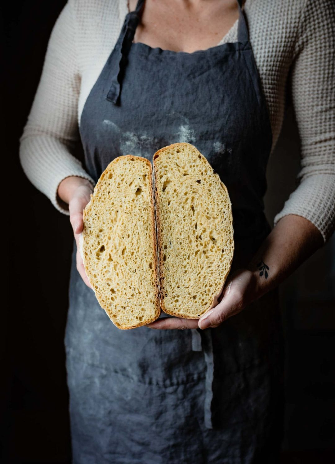 Chef holding a sliced artisan bread loaf.