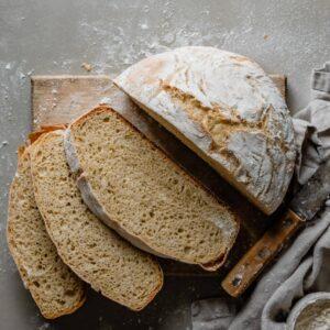 Sliced artisan bread loaf on cutting board.