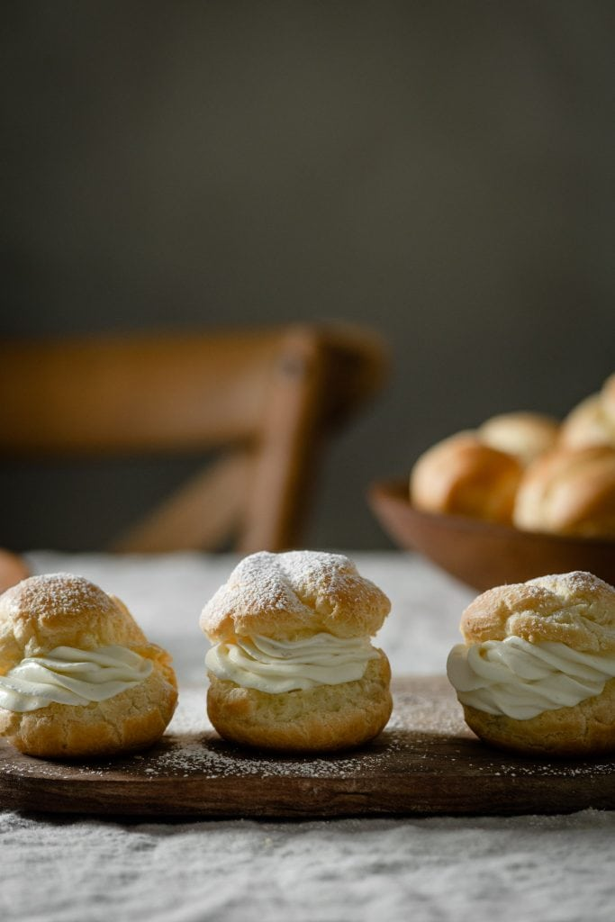 Banana cream filled choux pastry on cutting board.