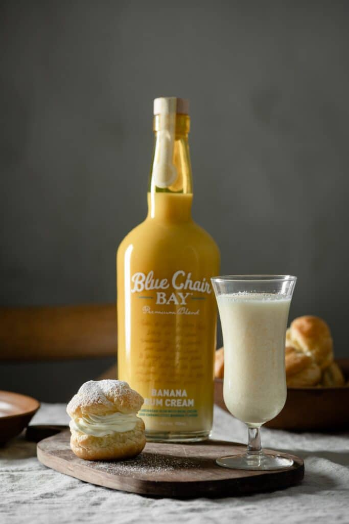 Blue Chair Bay Rum bottle with a cocktail and cream puff on table.