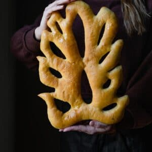 Lady holding a wheat shaped fougasse bread.