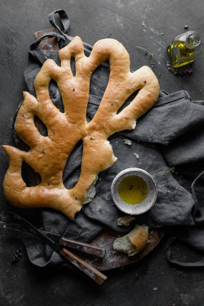 Fougasse flatbread with dipping oil on table.