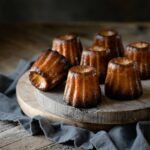 French Caneles on a wood board.
