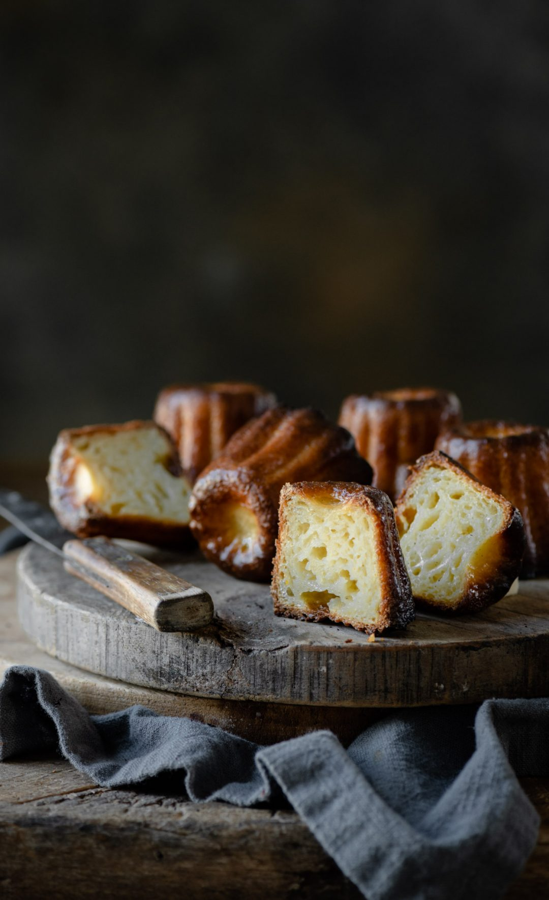Sliced rum caneles on cutting board.