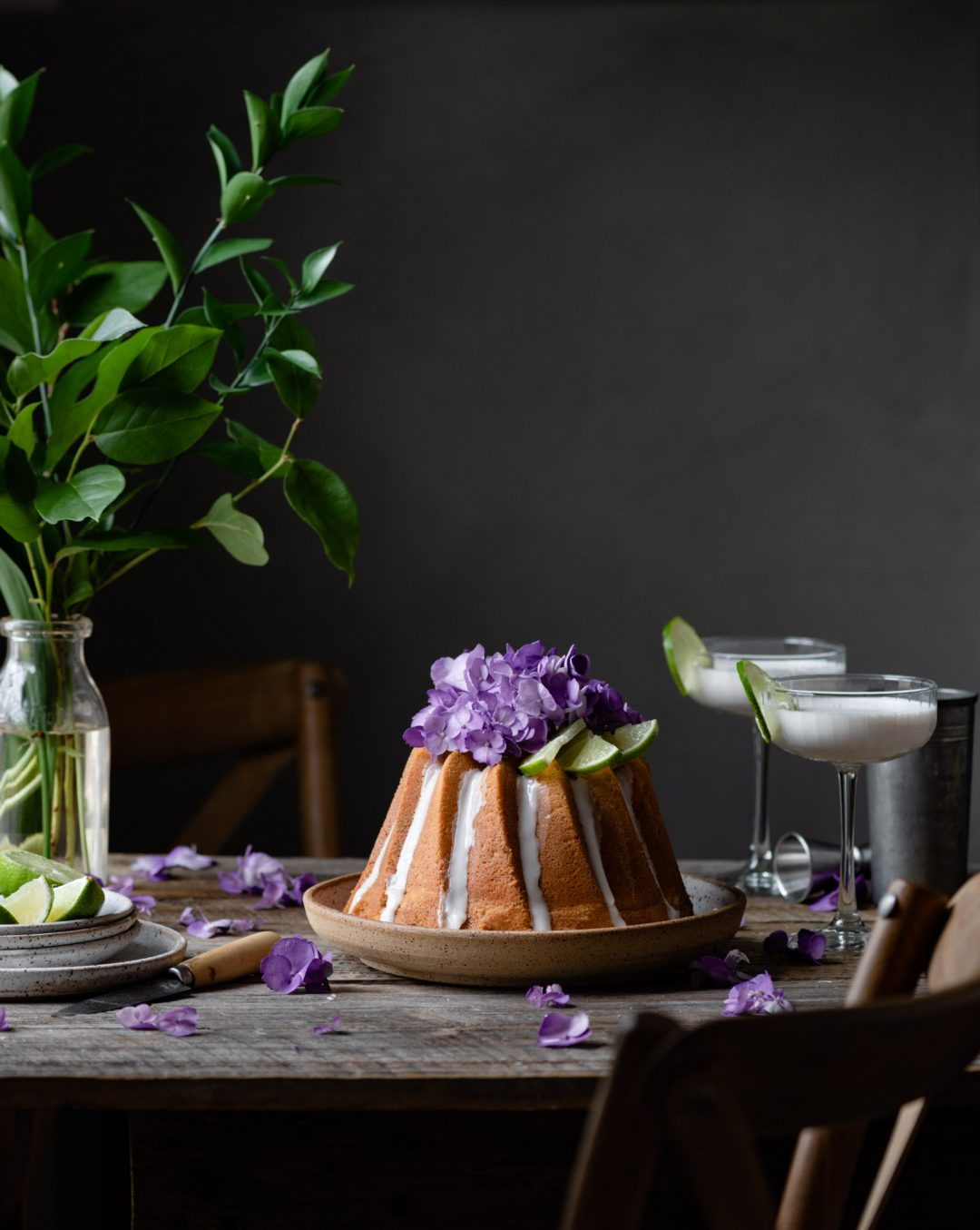 Key Lime Cake on table with flowers and cocktails.