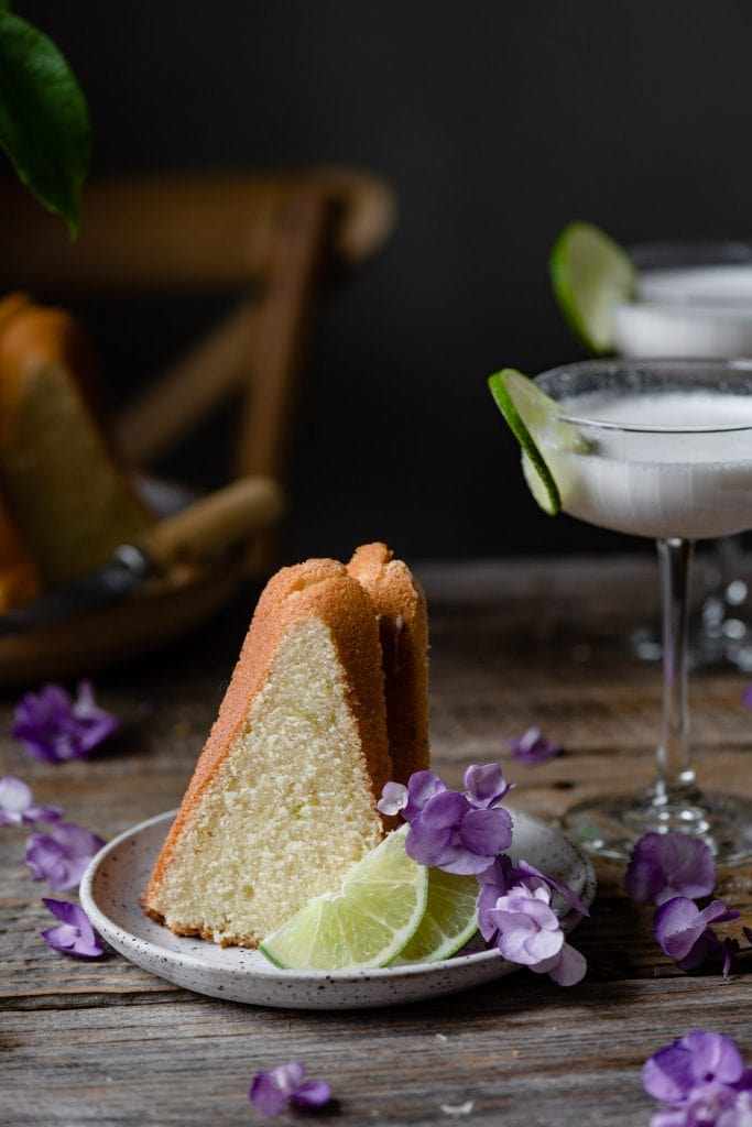 Slice of cake on plate with limes and purple flowers.