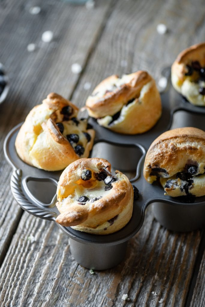 Blueberry popovers in popover tin on table.