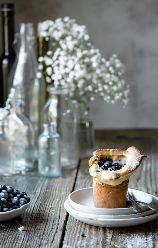 Single popover on a stack of plates on wood table next to flowers and a bowl of blueberries.