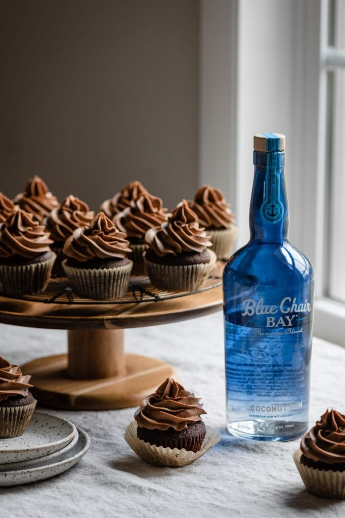 Bottle of rum on table next to cupcakes.