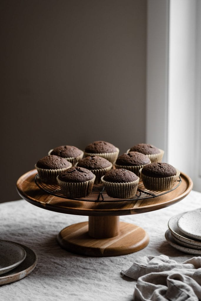 Cake stand with unfrosted chocolate cupcakes.