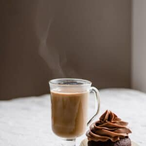 Hot coffee cocktail on table with a cupcake.