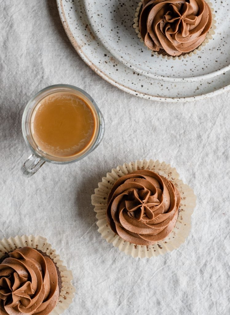 Chococlate frosted cupcakes on table with coffee cocktail.