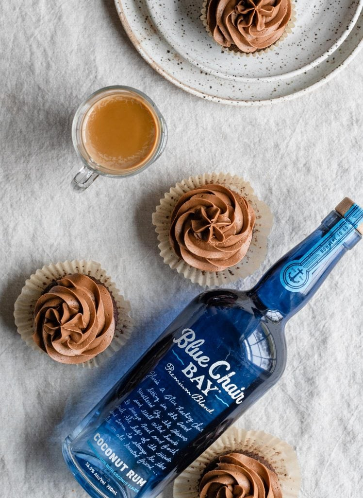 Chocolate cupcakes and a bottle of coconut rum on table.