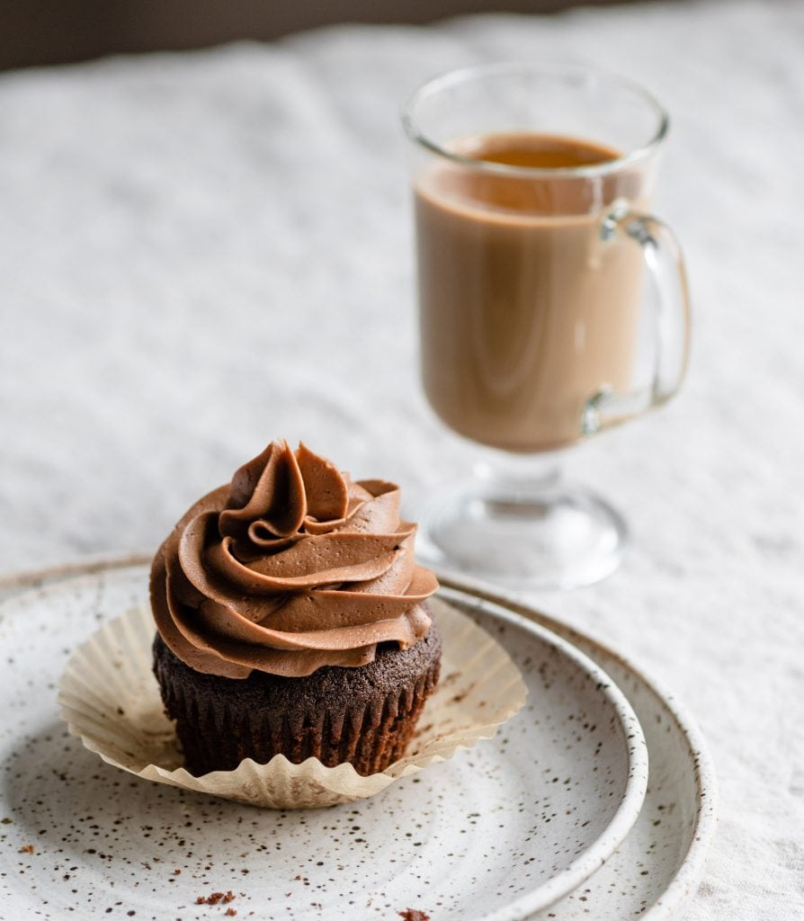 Chocolate cupcake on table next to coffee cocktail.