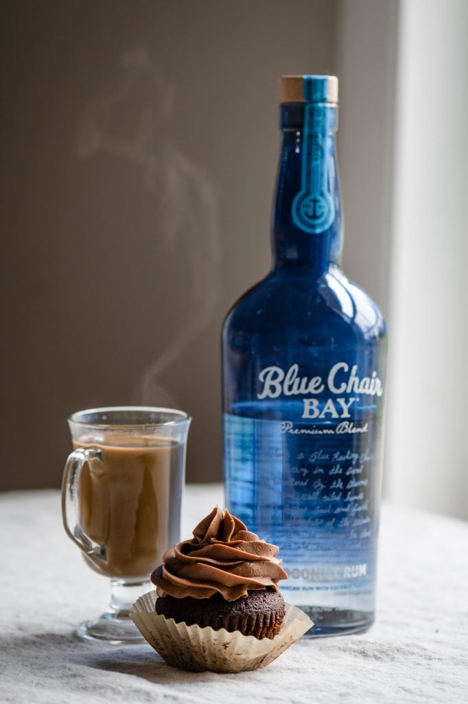 Hot coffee cockltail with a bottle of rum on table.