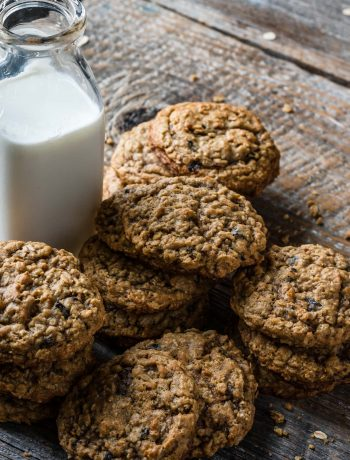 Cookies stacked on table with glass of milk.