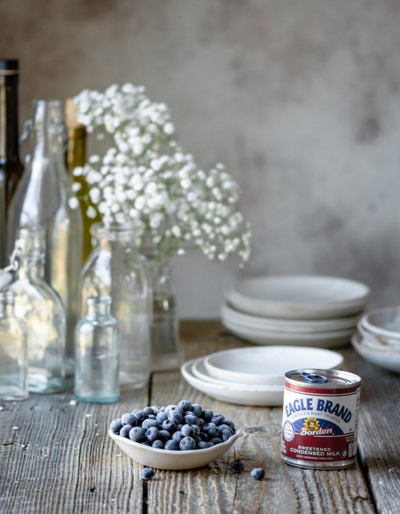 Sweetened condensed milk jar and fresh blueberries on table.