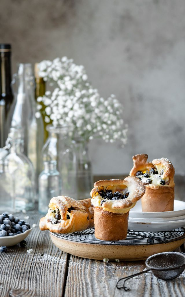 Blueberry popovers on table with bowl of fresh blueberries.