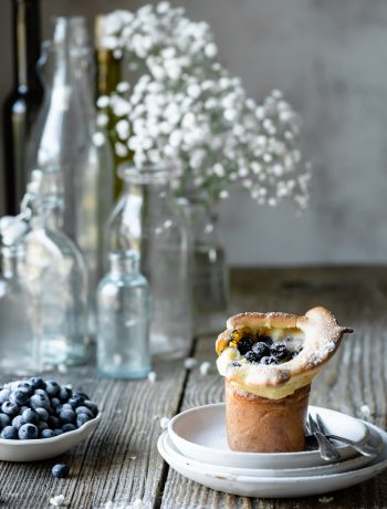 Blueberry Popover on table next to bowl of blueberries.