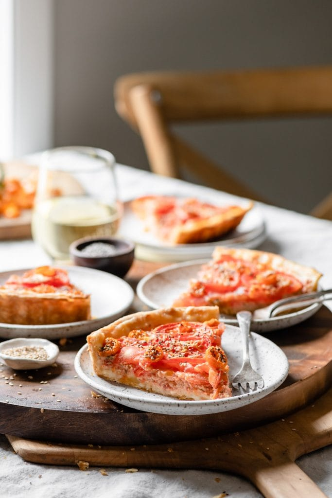 Slices of tomato tart with glass of wine.