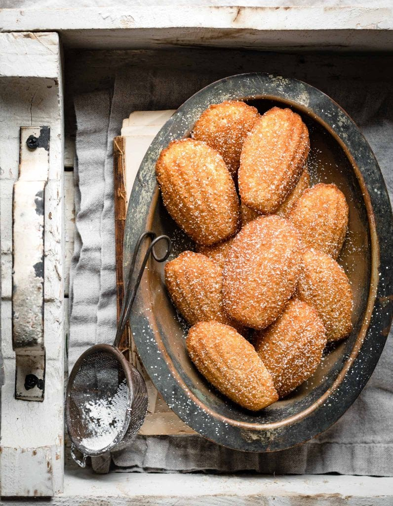 Shell shaped madeleines dusted with sugar in a bowl.