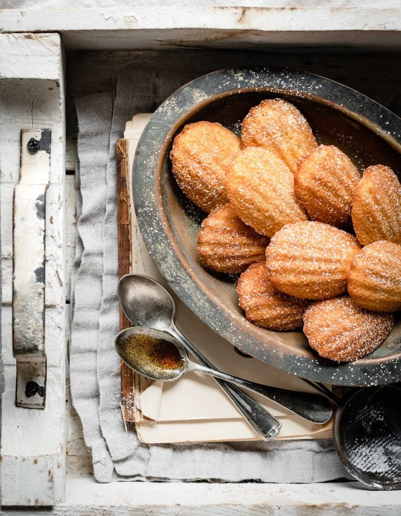 French madeleines on a plate with spoonful of vanilla extract.