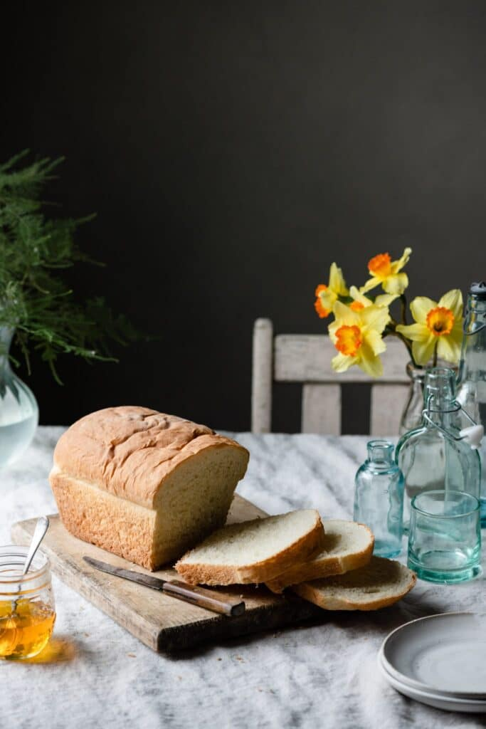 White bread on cutting board next to flowers.