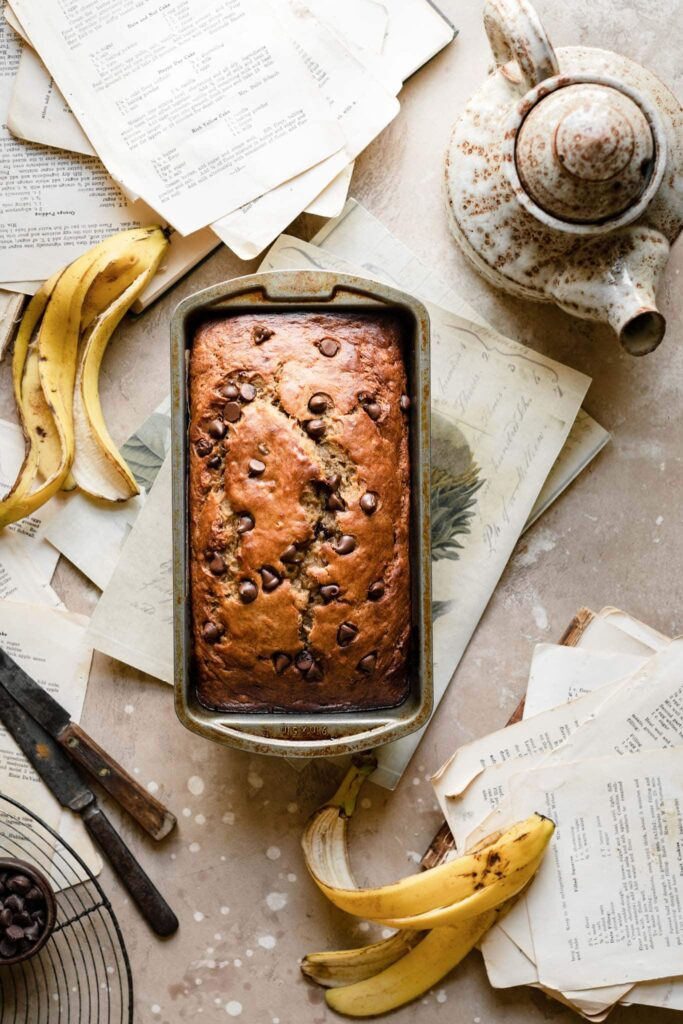 Loaf of banana bread on table with banana peels.
