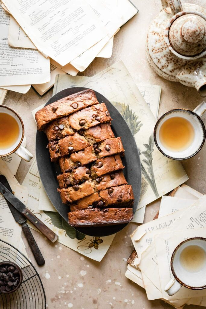 Sliced chocolate banana bread on plate with cups of tea.