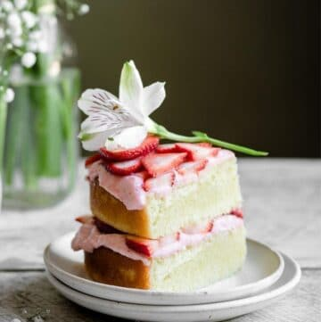 SLice of lemon cake with pink frosting topped with a flower.